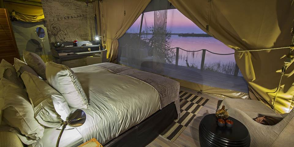 Luxury bedroom with river view at Duma Tau safari camp