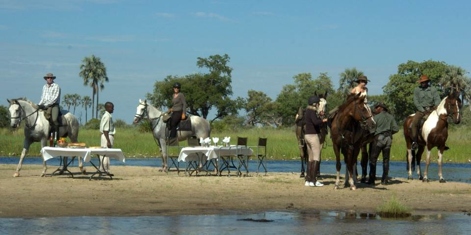 River side picnic for horse safari party from Macatoo camp Botswana