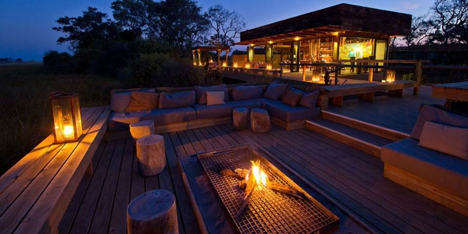 Outside decked area & fire at Vumbura Plains safari camp Botswana